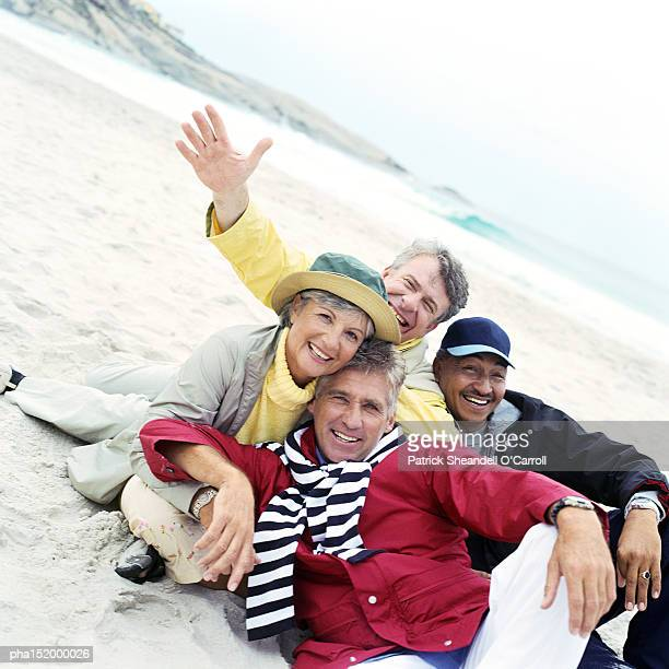 Mature group sitting on beach looking into camera.