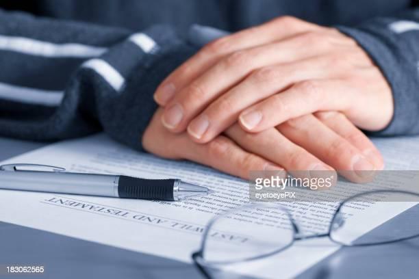 Ältere Hände mit letzten Willen und testament