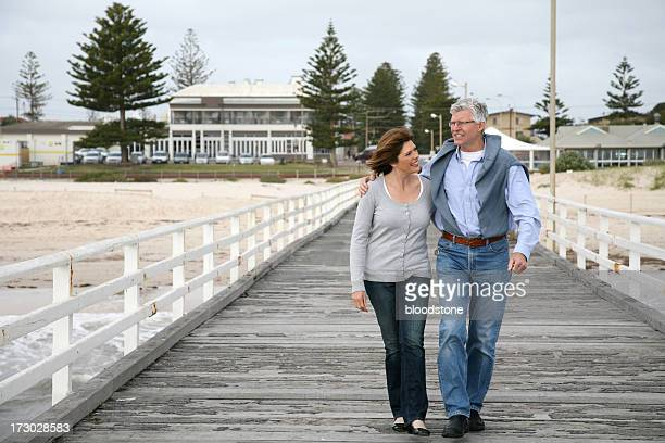 Mature heterosexual couple walking on dock