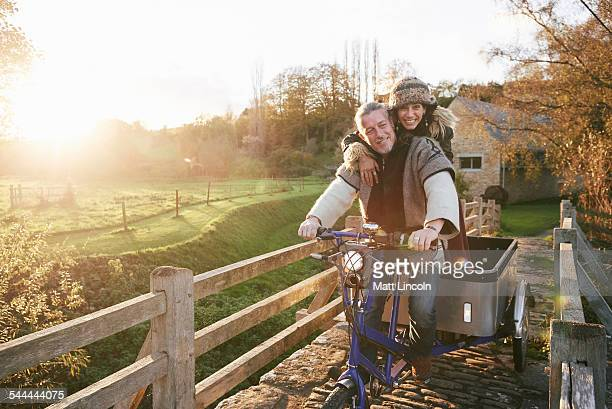 Mature hippy couple on tricycle and trailer on rural road