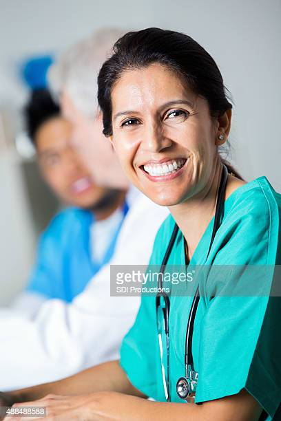 Mature Hispanic female doctor in meeting with hospital staff