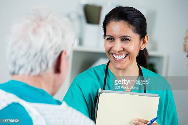 Mature Hispanic nurse assisting senior patient in hospital