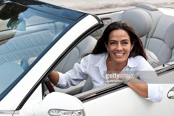 Mature hispanic woman driving a convertible