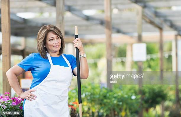 Mature Hispanic woman working in plant nursery