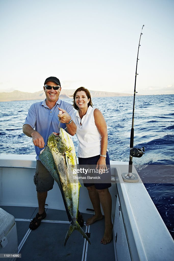 Mature husband wife couple holding catch on boat
