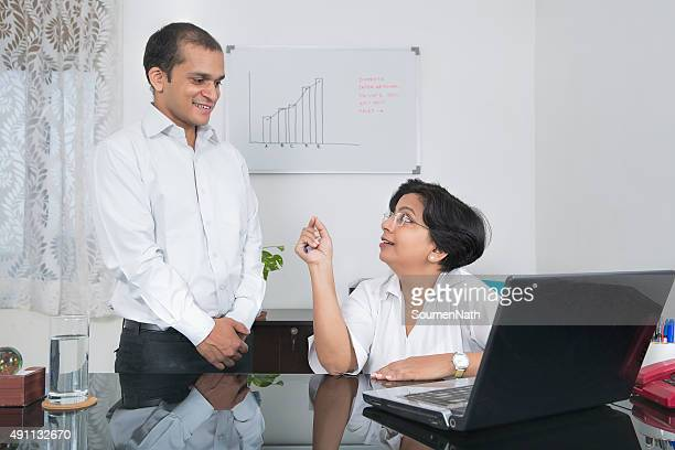 Mature Indian businesswoman giving Instructions to Subordinates at her office.