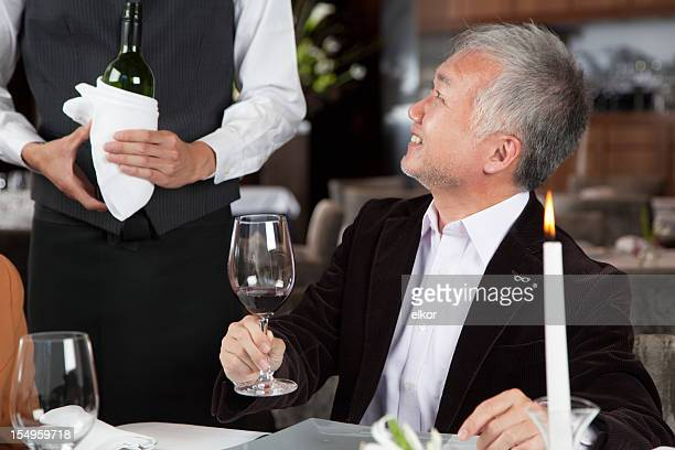 Mature Japaneese restaurant guest testing red wine.