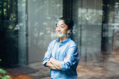 Mature Japanese businessman standing near glass in office