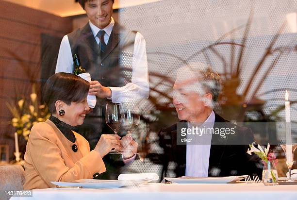 Mature Japanese couple dining at a restaurant seen through window.