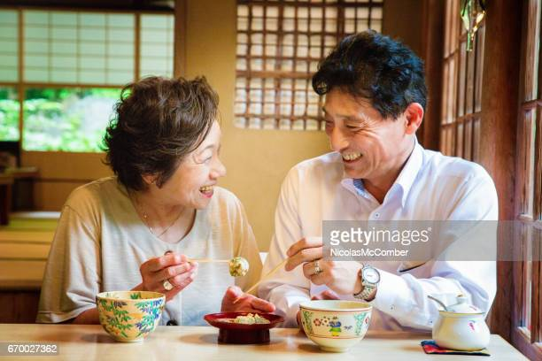 Mature Japanese couple laughing as they share delicacy