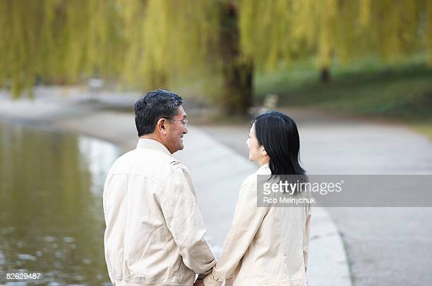 Mature Japanese couple walking in a park.