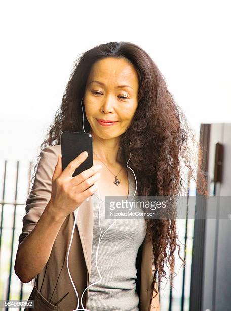 Mature Japanese female on outdoors video conference using mobile phone