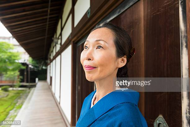 Mature Japanese Woman in Looking Up in Temple Kyoto Japan