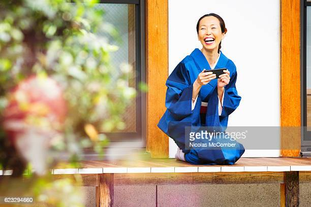 Mature Japanese woman laughing out loud at media on phone