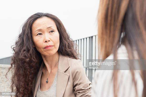 Mature Japanese Woman Listening to Coworker with Look of Concern