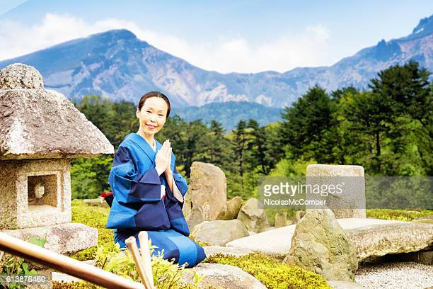 Mature Japanese woman praying portrait at country garden