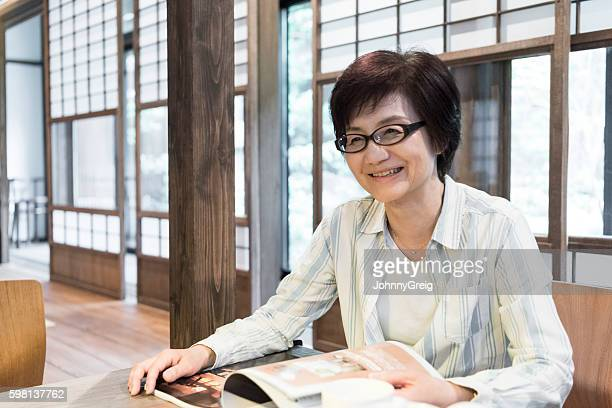 Mature Japanese woman with magazine, smiling