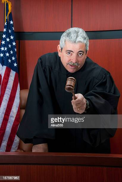Mature judge at the bench with serious look pointing gavel