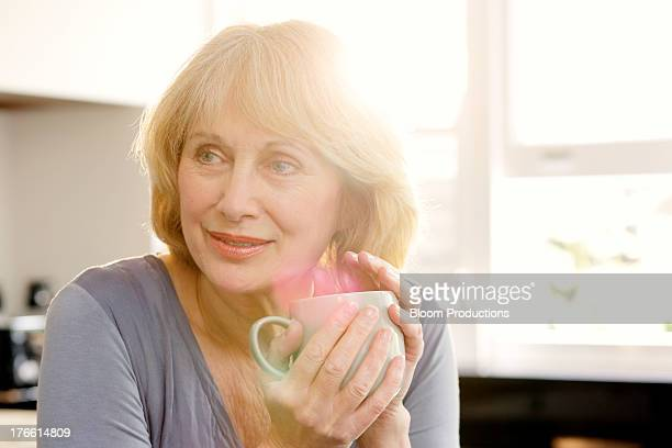 Mature lady holding a mug of coffee