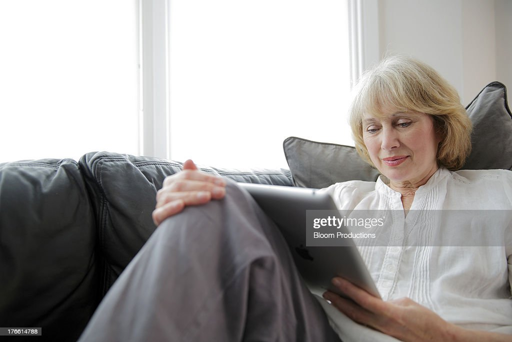 Mature lady using a tablet : Stock Photo
