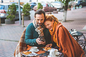 Cute middle-aged lovers are having breakfast in restaurant outside. They are sitting and holding hands. Man is using smartphone and smiling. Woman is laying head on his shoulder