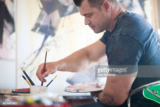 Mature male artist working on canvas in studio