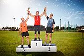 Mature male athletes on winners podium