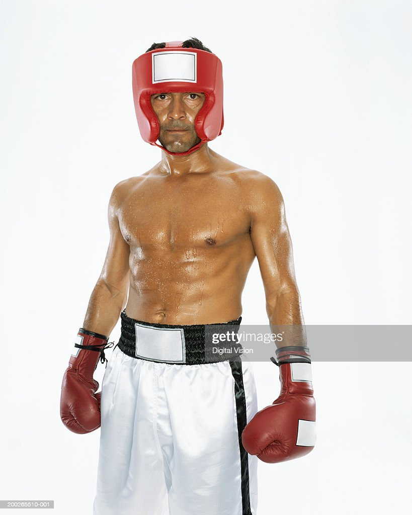 Mature male boxer wearing head protection, portrait : Stock Photo
