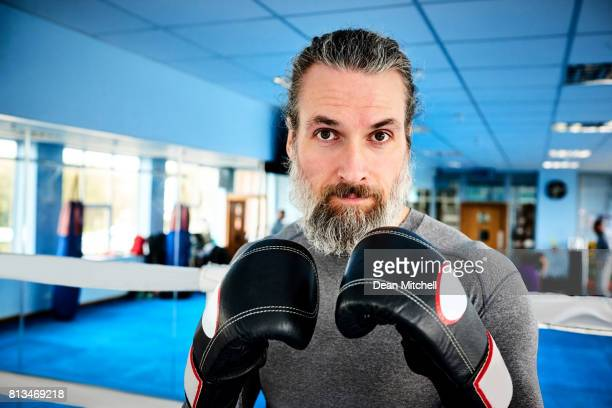 Mature male boxer with raised hands in gloves at gym