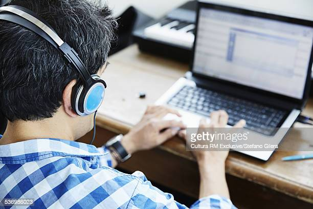 Mature male composer typing on laptop in music studio