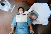 Mature male dentist examining boy's (10-12) teeth, overhead view