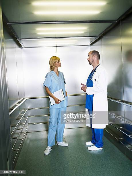 Mature male doctor and female nurse in lift