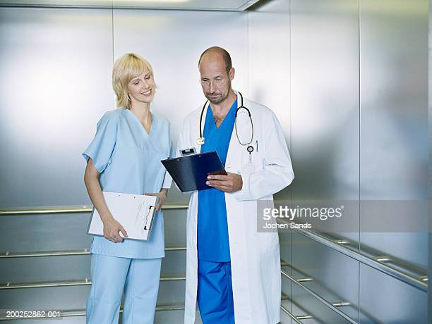 Mature male doctor and female nurse looking at clipboard in lift
