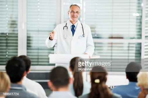 Mature male doctor giving a speech on seminar