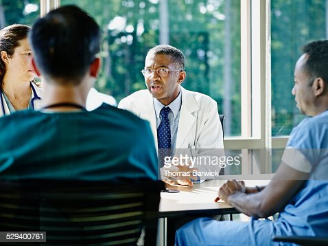 Mature male doctor leading medical team meeting