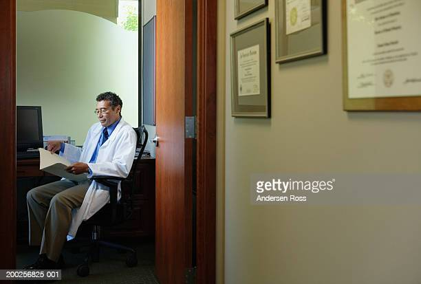 Mature male doctor looking at medical chart in office, side view