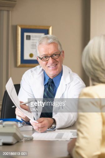 Mature male doctor showing woman report at desk in office : Stock Photo