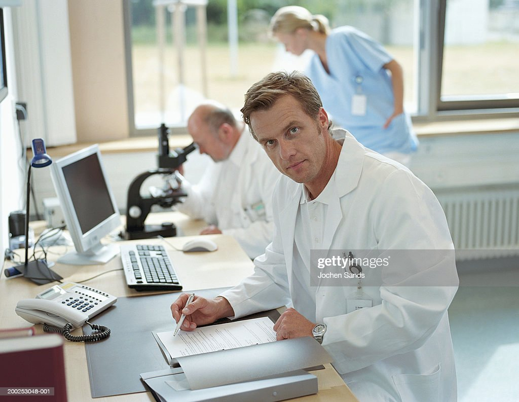 Mature male doctor sitting in office, portrait : Stock Photo