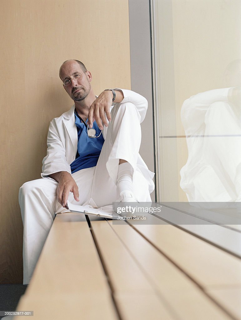 Mature male doctor sitting on window sill, portrait : Stock Photo