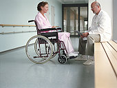 Mature male doctor talking to female patient in wheelchair