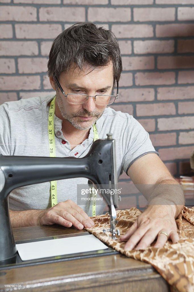 Mature male dressmaker stitching cloth on sewing machine : Stock Photo
