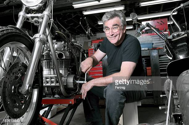 Mature male enjoying working on a classic motorcycle
