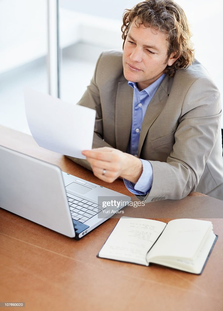 Mature male executive reading document : Stock Photo