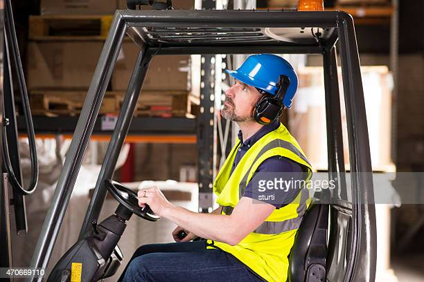 mature male forklift truck driver looking up at his pallet.