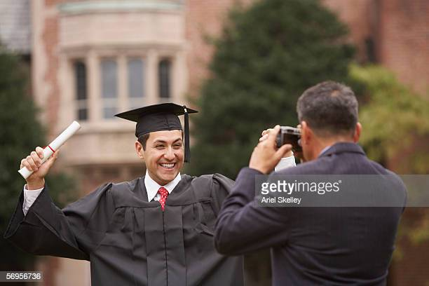Mature male graduate in cap and gown with diploma