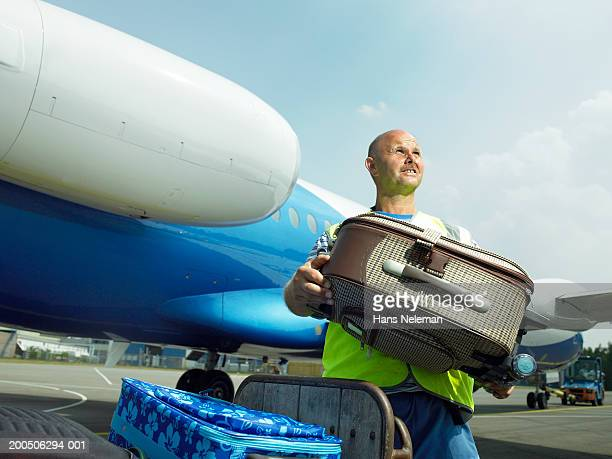 Mature male luggage official by airplane