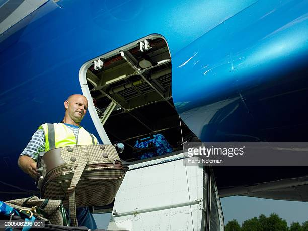 Mature male luggage official carrying suitcase by plane