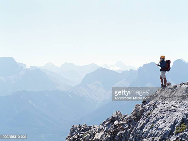 Mature male mountaineer using mobile phone on mountain peak, side view