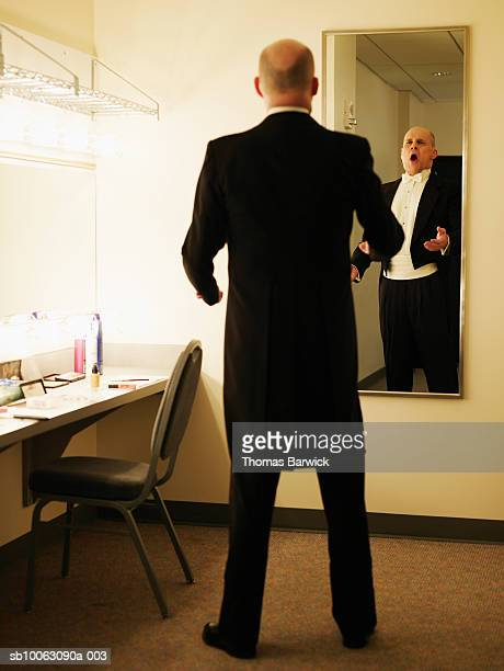 Mature male opera singer warming up in dressing room mirror
