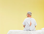 Mature male patient sitting on gurney in hospital gown, looking to side, rear view